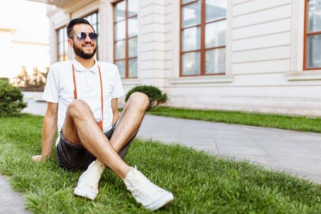 Стильный хипстер с фотоаппаратом на шее, сидящий на газоне в парке