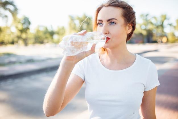 Молодая спортивная девушка, пьющая воду из бутылки, после тяжелой тренировки.