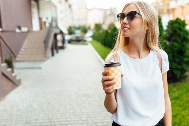屋外と一杯のコーヒーを保持している若い女性の肖像画。街を歩いて、コーヒーを飲む女の子。