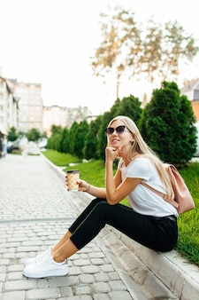 屋外でコーヒーを飲みながらサングラスをかけている若い女性の肖像画。芝生の上に座ってコーヒーを飲む女の子。