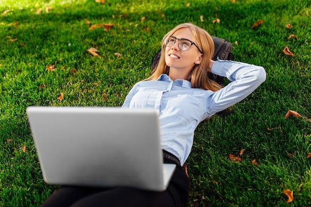 ラップトップコンピューターで公園の芝生の上に横たわっているメガネで物思いにふける女の子、何かの夢