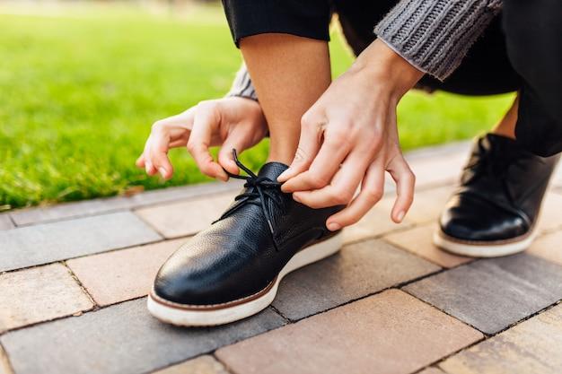 Девушка завязывает шнурки на мокасинах на улице