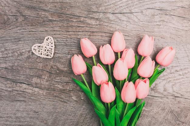 Букет из розовых тюльпанов и маленькое белое плетеное сердце на деревянном фоне