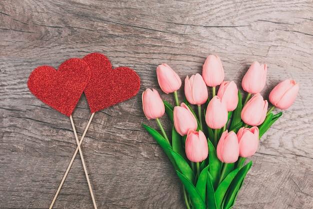 Букет из розовых тюльпанов и красных двух сердец из бумаги, на деревянном фоне