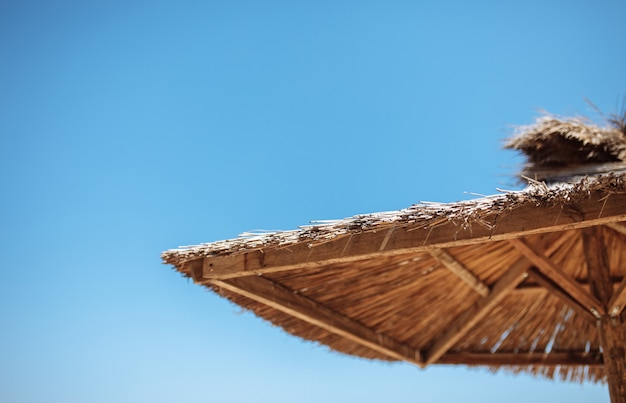 Солома и деревянный зонт на голубом небе