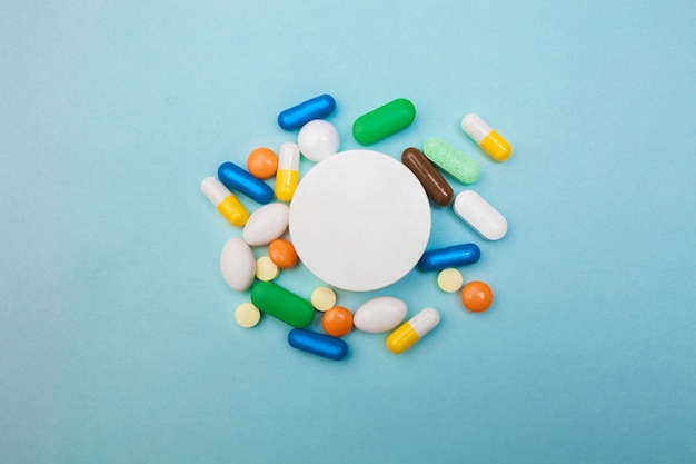 Разноцветные таблетки и капсулы и белая бутылка для таблеток