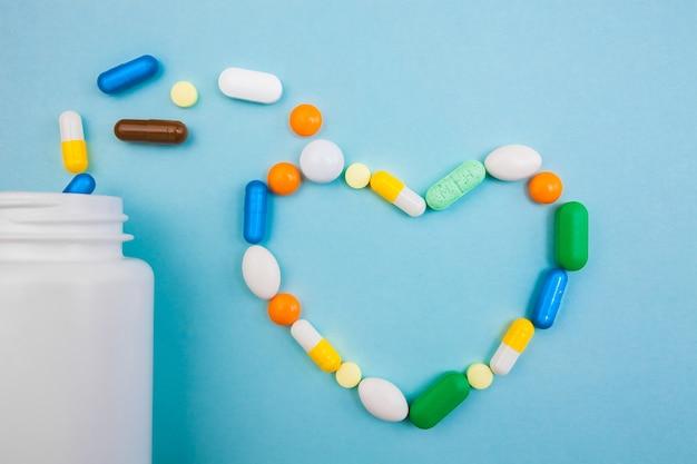 Разноцветные таблетки и капсулы в форме сердца с белой бутылкой для таблеток