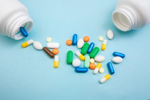 Разноцветные таблетки и белая бутылка для таблеток