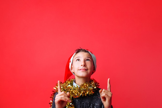 Портрет подростка в новогодней шапке и с мишурой на шее вверх