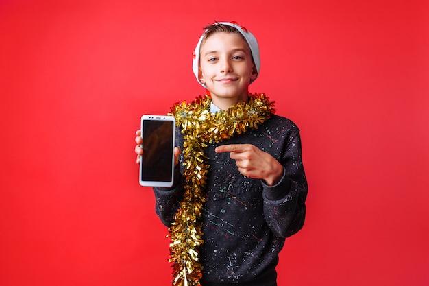 Позитивный подросток в шапке деда мороза с мишурой на шее показывает смартфон