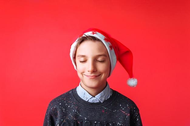 Красивая девушка в шапке санты, улыбаясь с закрытыми глазами, загадывает желание на новый год