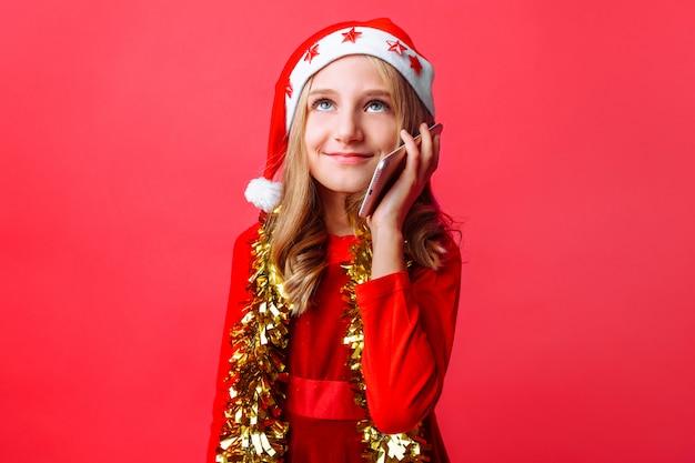 Счастливая девушка в красной шапочке санты и с мишурой на шее