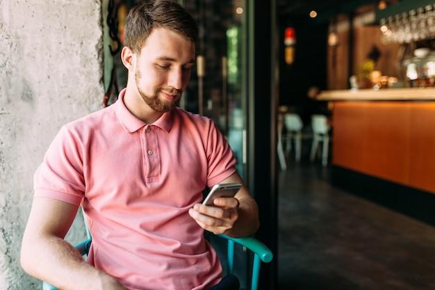 ノートパソコンと携帯電話、作業、オンラインショッピング、流行に敏感なカフェに座っている若い男