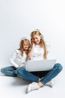 私のラップトップで映画を見て、楽しんで、笑っている姉または若い母親と娘