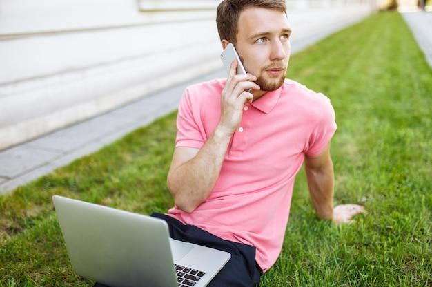 ノートパソコンで街の芝生の上に座っていると、就職活動、電話で話しているハンサムな男