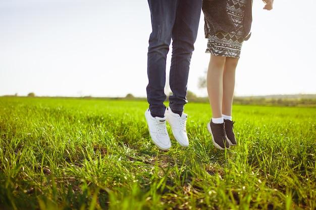 Молодые, счастливые, любящие пары, на природе, фото ног в прыжке, и наслаждаемся друг другом