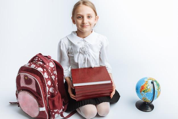 Маленькая милая школьница, сидящая с книгами и земным шаром, улыбающаяся и счастливая
