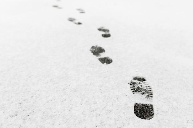 男が歩いた、彼は雪の中に足跡を残しました