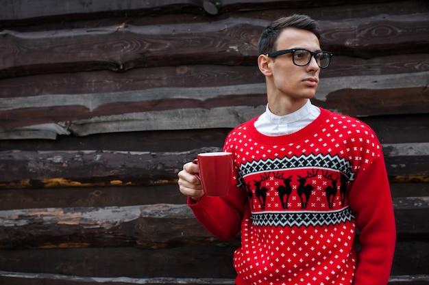 木製の壁の背景に、コーヒーを飲みながらクリスマスセーターの少年のポートレート