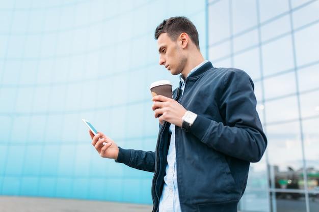 コーヒーの紙コップを持つ男は、電話を手にスタイリッシュな服を着たハンサムな男、街を通り抜けます