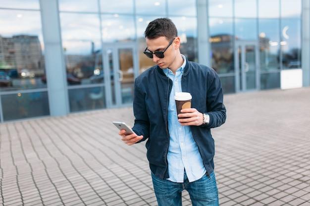 Мужчина с бумажной чашкой кофе, проезжает по городу, красивый парень в стильной одежде и солнечных очках, звонит по телефону