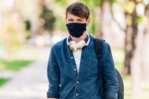 顔に防護マスクをかぶった男が首にワイヤレスヘッドフォンを付けて公園を歩きます。検疫、コロナウイルス