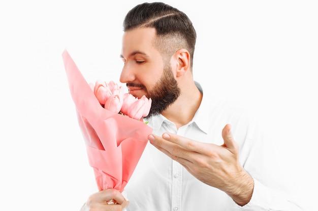 バレンタインデーのギフト、チューリップの花束を持ったひげを持つエレガントな男