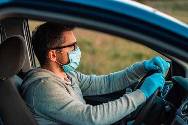 Молодой человек в защитной маске и медицинские перчатки за рулем в машине