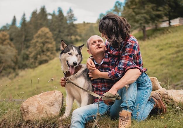 夏休みを楽しんでハスキー犬と男性女性。