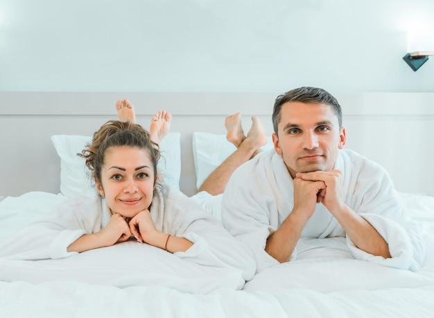休暇中にホテルの部屋のベッドで横になっている白いバスローブの新婚旅行の旅行者