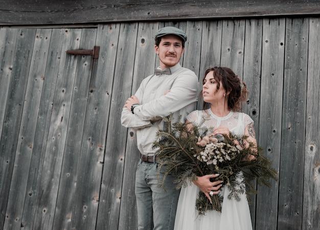 灰色の木製の壁の近くのビンテージスタイルに身を包んだ新婚夫婦