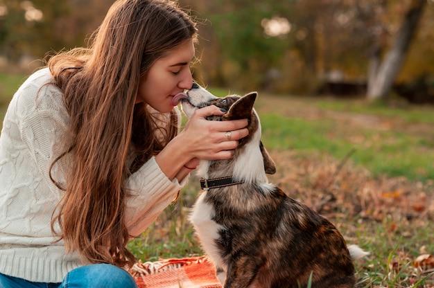 Молодая женщина-владелец обнимает свою собаку вельш корги на красном пледе в осеннем парке