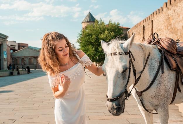 Милая кудрявая девушка возле старого замка в европе.