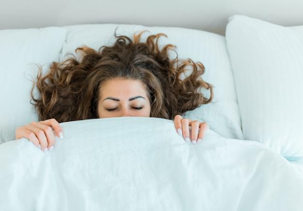 高級マンションの白いベッドでセクシーな若い大人の女性の官能的なブルネットの女性ヌード。贅沢で豊かなライフスタイル。クローズアップショット。
