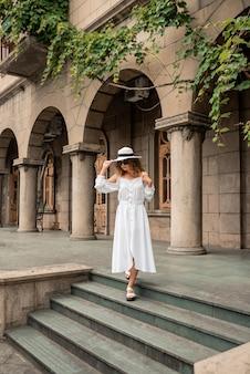 旧市街を探しているファッションの女の子の女性。ヨーロッパの女の子。旅行の概念。白いドレスと帽子で美しい少女。通りの背景にファッションモデル。ライフスタイル、旅行、休暇、観光
