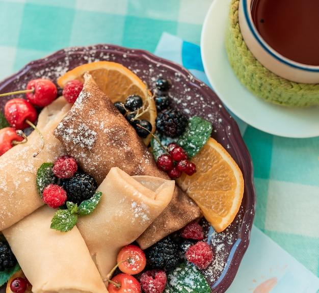 果実と新鮮なパンケーキ。茶色のプレートに森の果実の果実とパンケーキ。