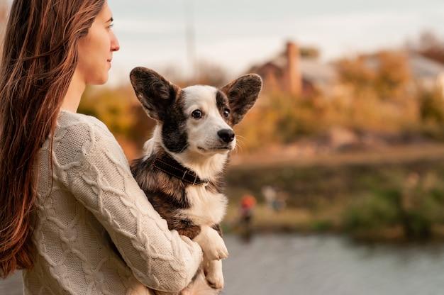 ペットのウェールズコーギー犬を抱いて笑顔の女性
