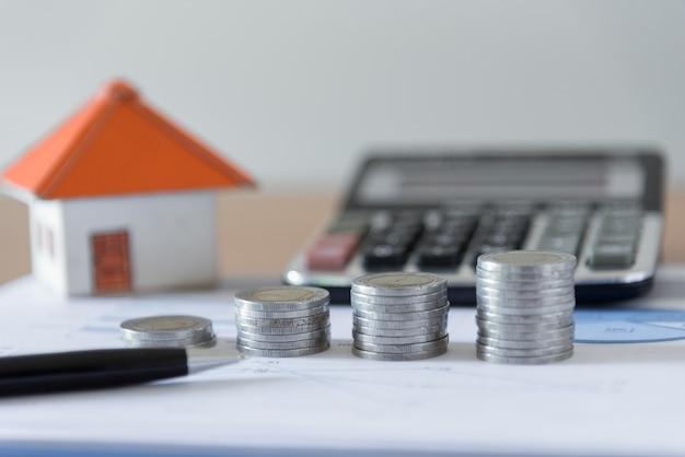 ペン、ペーパーハウス、ビジネス文書のチャートのオフィスデスクの背景に電卓とコインスタック