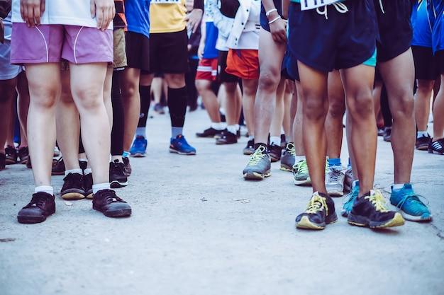 スタートラインの若者マラソンランナーのグループ。