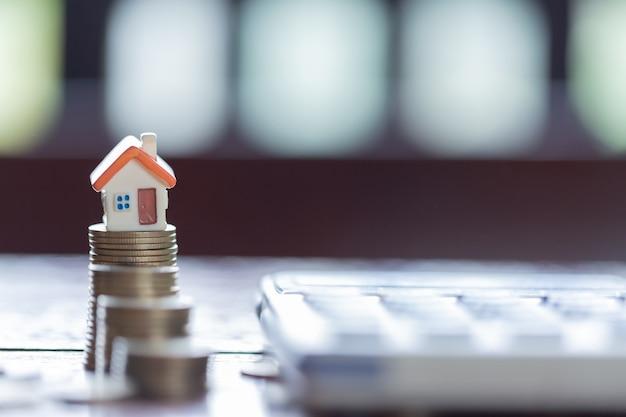 家のモデルとコインは、背景として電卓を積み重ねます。プロパティラダーの概念。