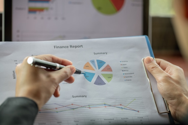 Деловой человек, анализируя финансовую статистику отображается на миллиметровой бумаге