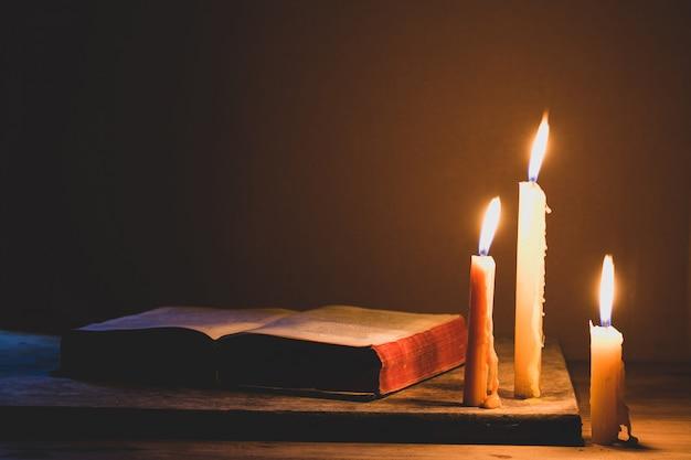 聖書と古いオーク木製のテーブル上のろうそく。美しいゴールドの背景。宗教の概念。