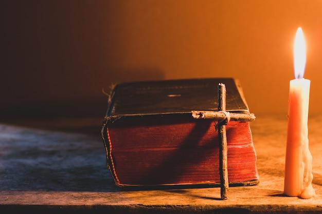 古いオークツリーの木製テーブルに聖書とろうそくと交差する。美しいゴールドの背景。