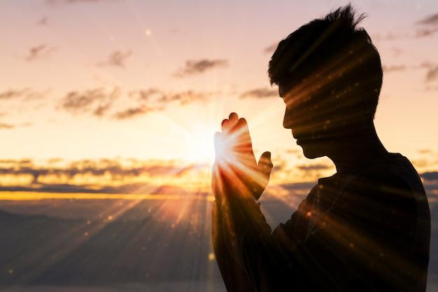 キリスト教の男の手の祈り、精神性および宗教、神に祈る人のシルエット。