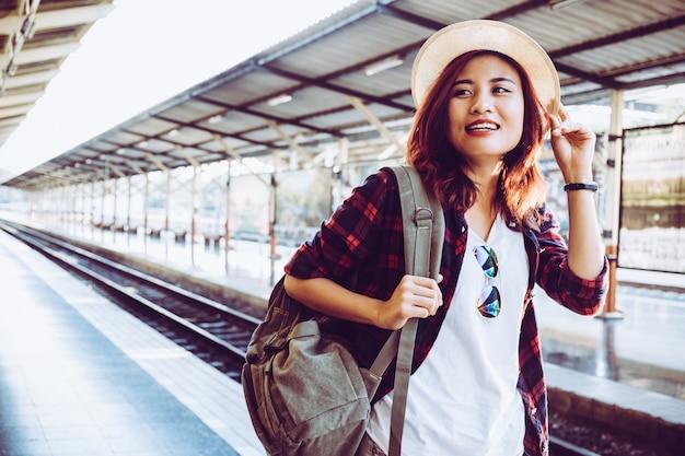 若い女性旅行者は、鉄道駅、サマーホリデーと旅行コンセプトで待っているバックパックを身に着けている