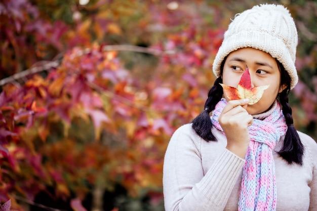 オレンジの葉を手に持って秋の公園で幸せな女の子