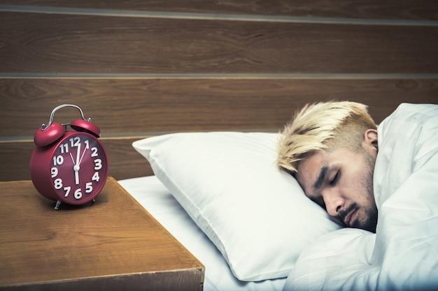 Часы на столе крупным планом, человек, просыпающийся