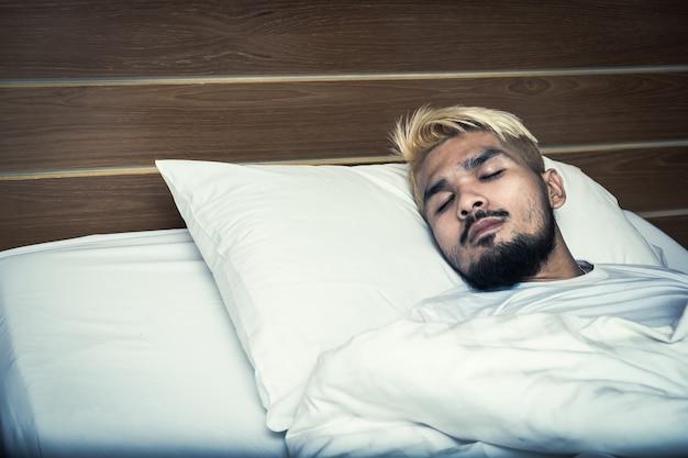 Красивый молодой человек, спящий в белом постельном белье