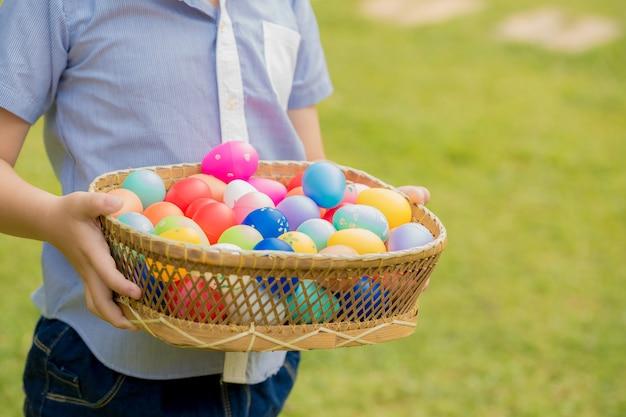 Маленький мальчик держит корзину, полную красочных пасхальных яиц