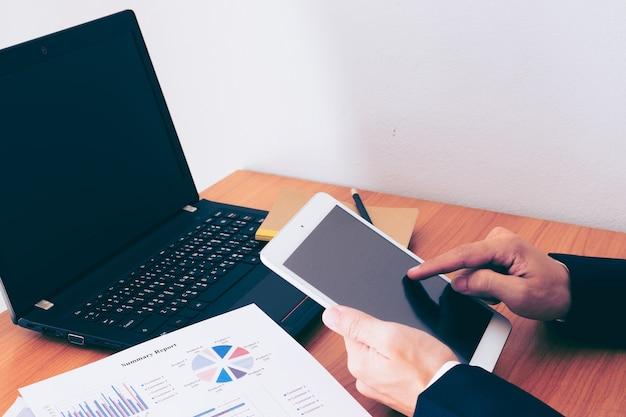 Деловой человек, работающий в офисе со смартфоном и документы на своем столе